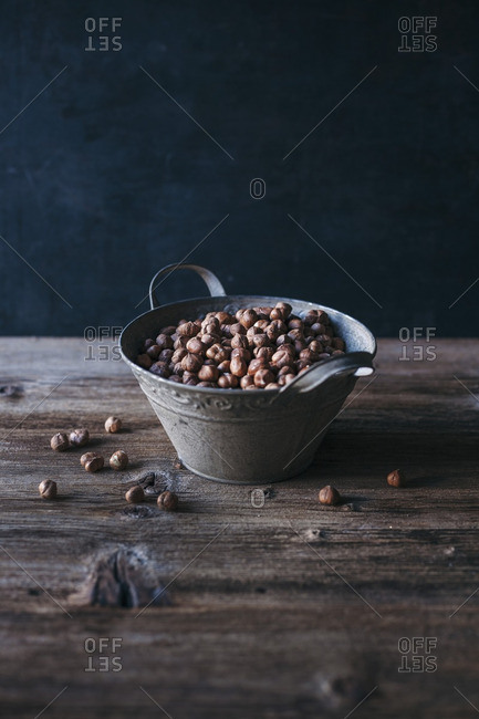 Raw hazelnuts in a metal bucket on a wooden table