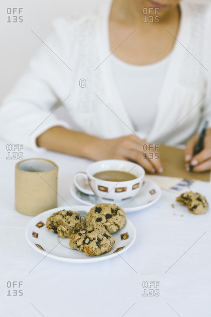 A woman writing a letter while having oatmeal cookies and coffee.