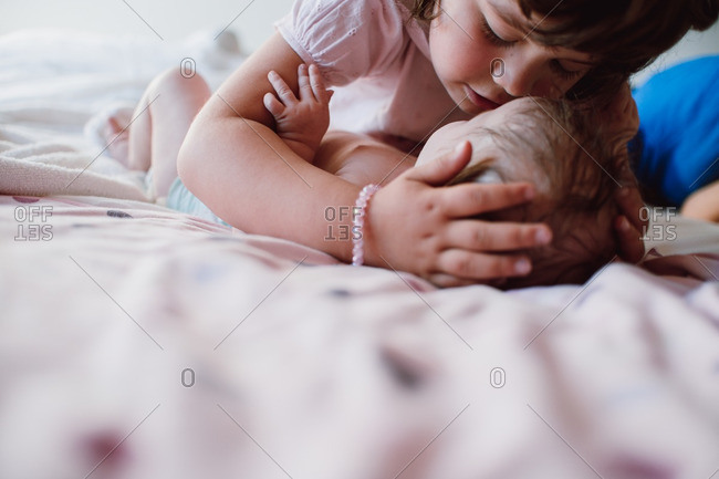 Girl giving her baby sister a kiss
