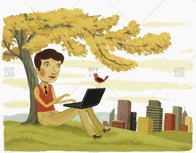 Man sitting in park using laptop