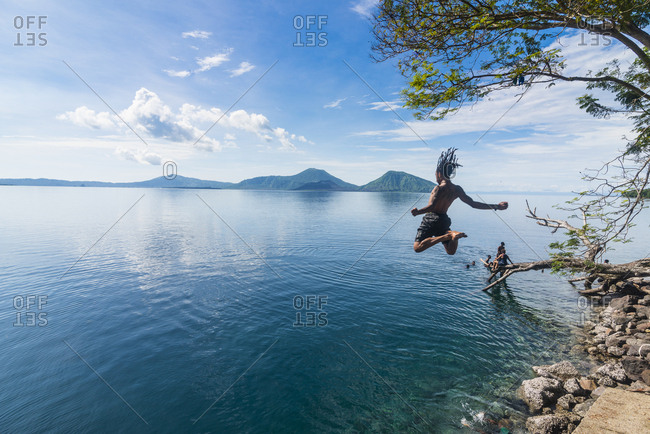 East New Britain, Papua New Guinea - June 25, 2016: Man jumping in the bay of Rabaul with Volcano Tavurvur in the background, East New Britain, Papua New Guinea, Pacific