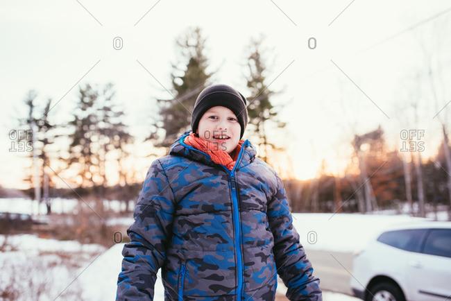 Boy on a snowy hill in a puffy jacket and toboggan