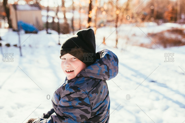 Boy in a toboggan and puffy jacket in the snow