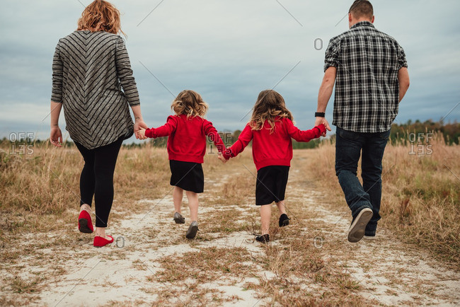 Parents and two daughters walking hand-in-hand on a rural path