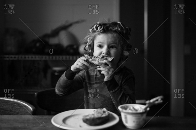 Girl eating breakfast with curlers in her hair