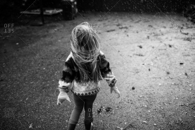 Little girl playing in the rain in black and white