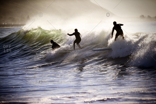 Surfers catching a wave