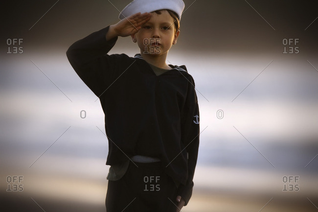 Young boy wearing a navy costume gives a salute