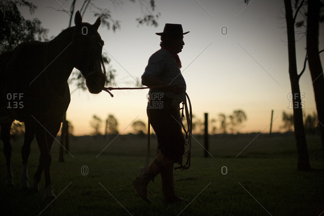 Rancher leading a horse at sunset