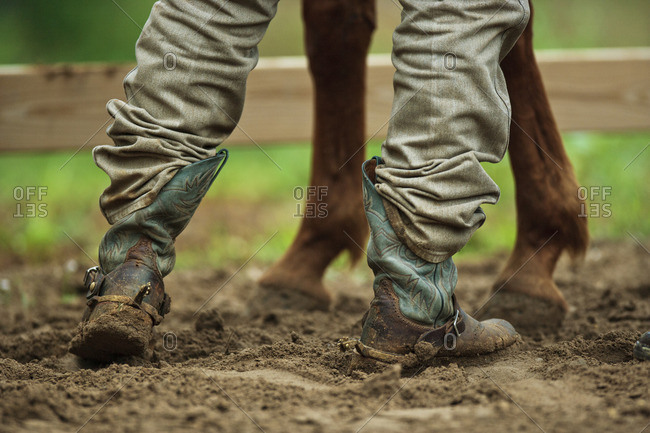 Person wearing cowboy boots tending to their horse