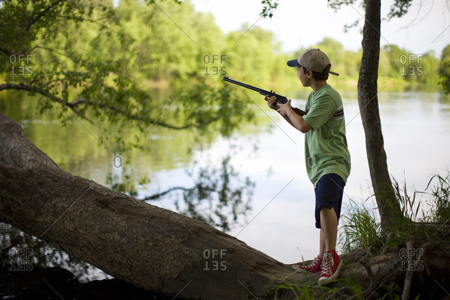 Young boy playing with a toy gun by a lake