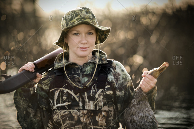 Young woman holding a dead duck she has shot while hunting