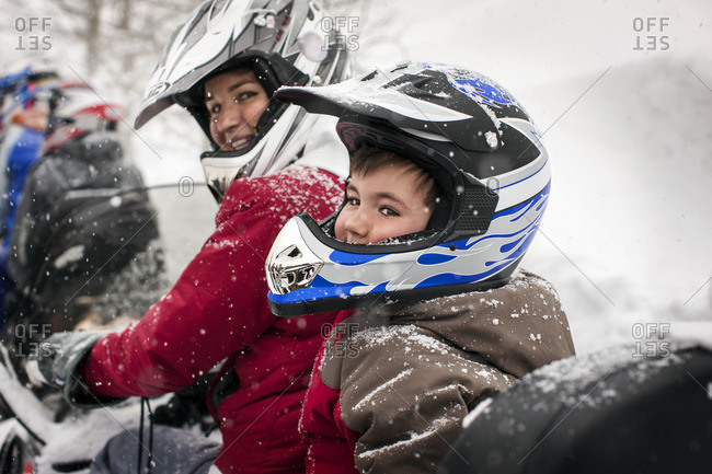 Mother and son riding a snowmobile together