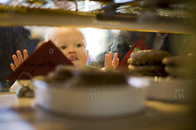 Baby boy looking at sweet treats in a display cabinet