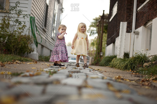 Two young sisters on the footpath outside their house