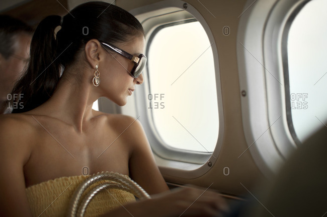 Young woman looking out the window of a plane