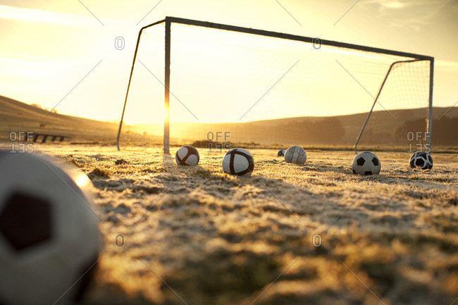 Soccer balls on a frosty field at sunset
