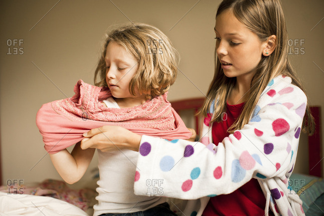 Young girl helping her little sister get dressed