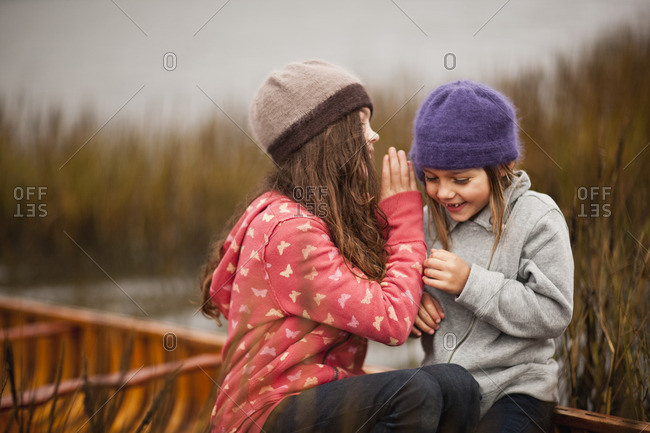 Two young girls laughing while whispering secrets