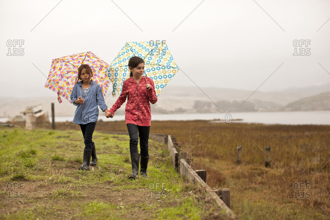 Two young girls walking hand in hand