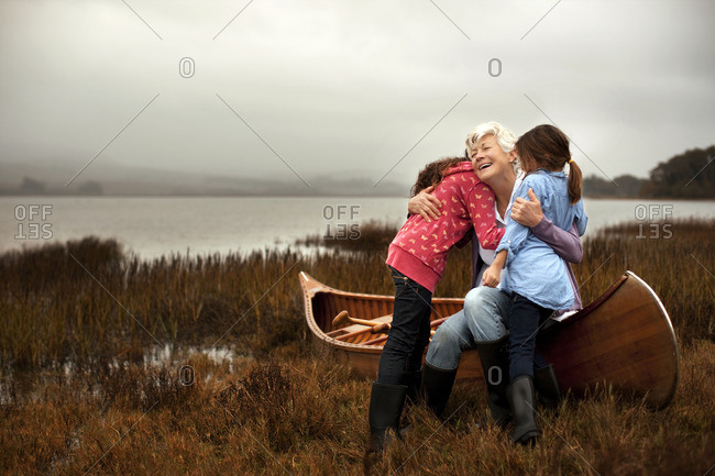 Granddaughter hugging her two granddaughters on a canoe