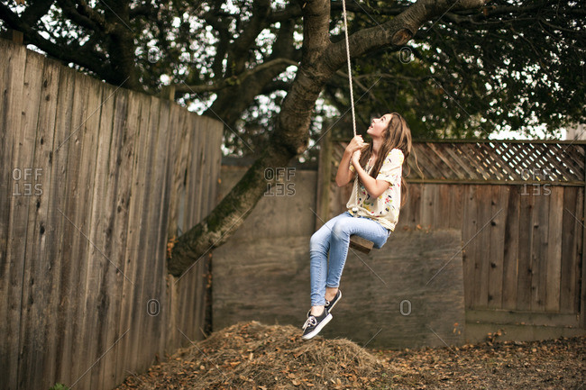 Young girl swinging on a tree swing