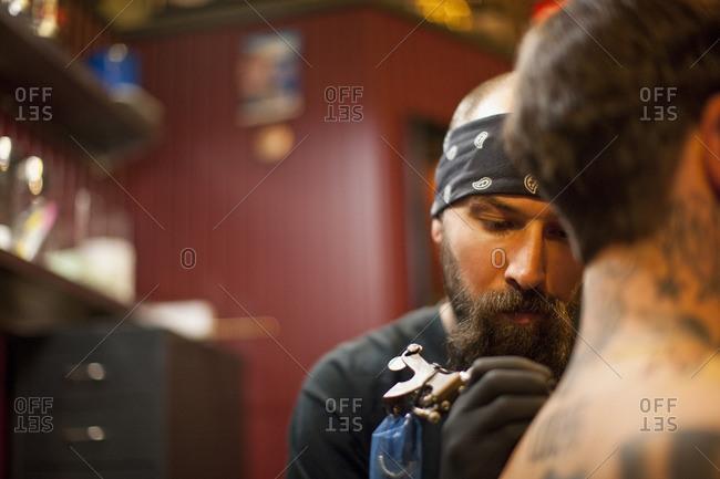Tattoo artist tattooing a client