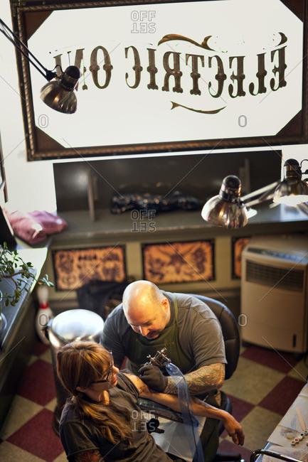 Tattoo artist tattooing a customer's arm