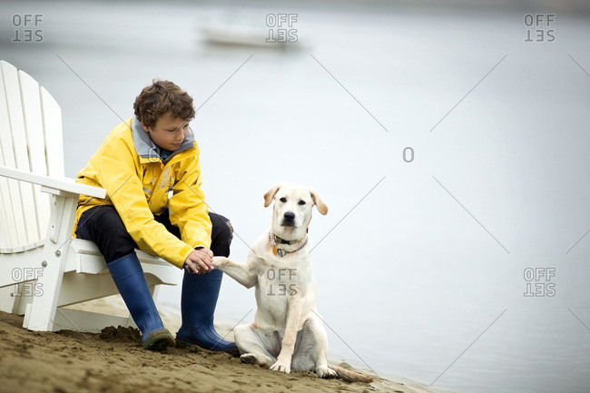 Young boy holding his dog's paw on the beach