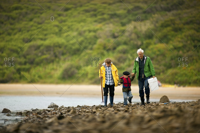 Grandparents walking with their grandson on a rocky beach