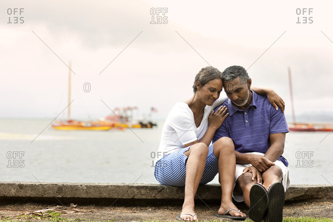 Worried couple sitting together by the harbor