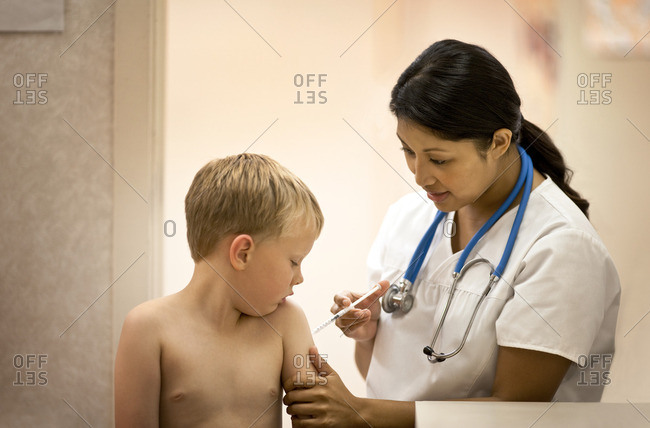 Nurse giving a young boy an injection