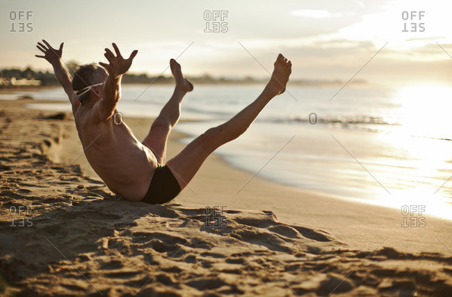 Senior man sitting on the beach with his arms and legs in the air