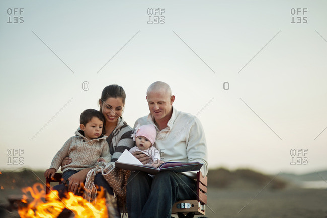 Family reading a book together by a campfire on the beach