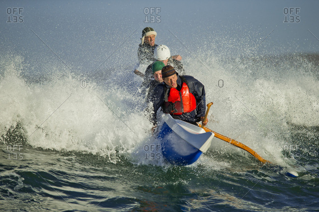 Team of canoeists catching a wave