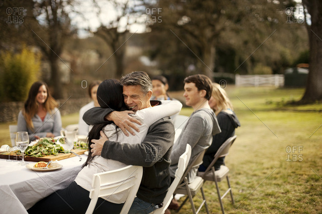 Friends hugging during an outdoor dinner party