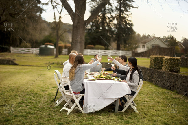 Group of friends making a toast during an outdoor dinner party