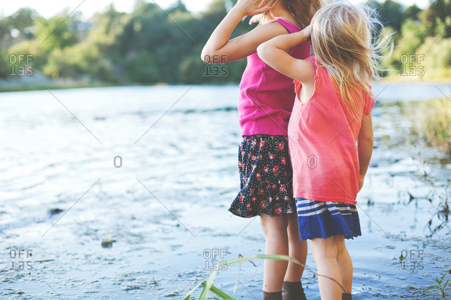 Two young girls wading in marshy pond