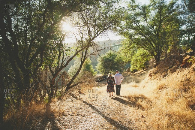 Couple walking hand in hand on path in wooded hills