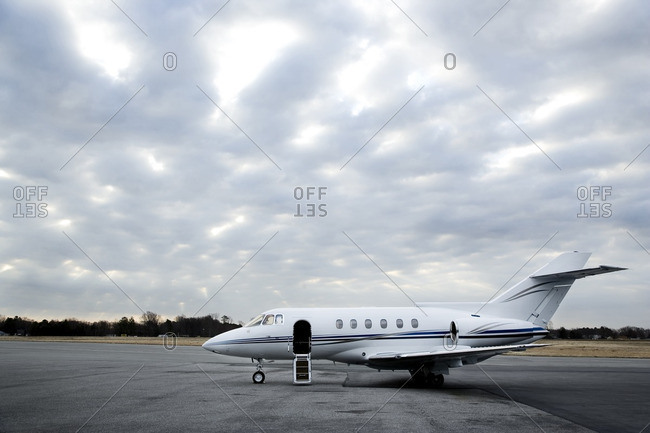 Private jet parked at airport under cloudy skies