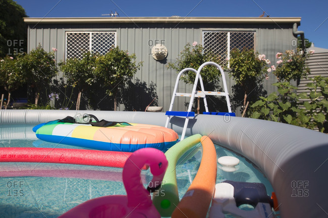 Pool toys and floats in a backyard inflatable swimming pool