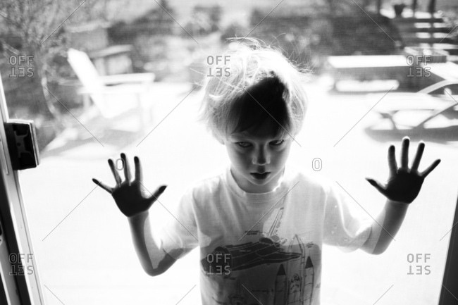 Boy standing with hands on screen door