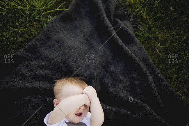Overhead view of baby on blanket covering eyes