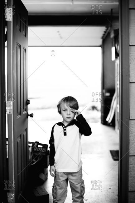 Boy rubbing his eye while standing in doorway to garage