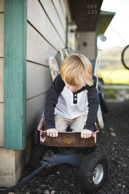 Boy playing in rusty wagon at side of house