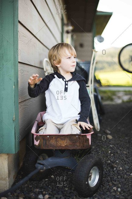 Little boy playing in wagon at side of house