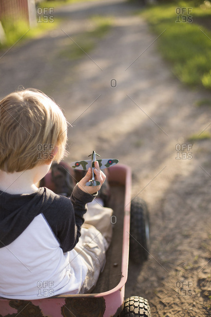 Back view of boy in wagon with toy airplane