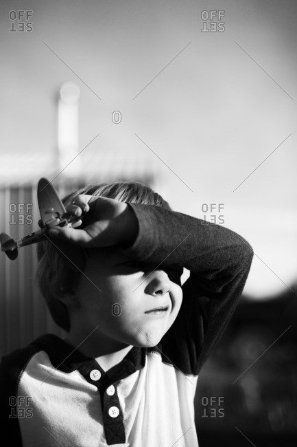 Boy with toy airplane shielding eyes from sun