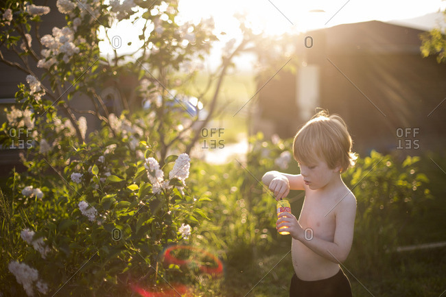 Shirtless young boy playing with bubbles in garden