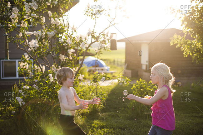 Two young children playing with bubbles in garden